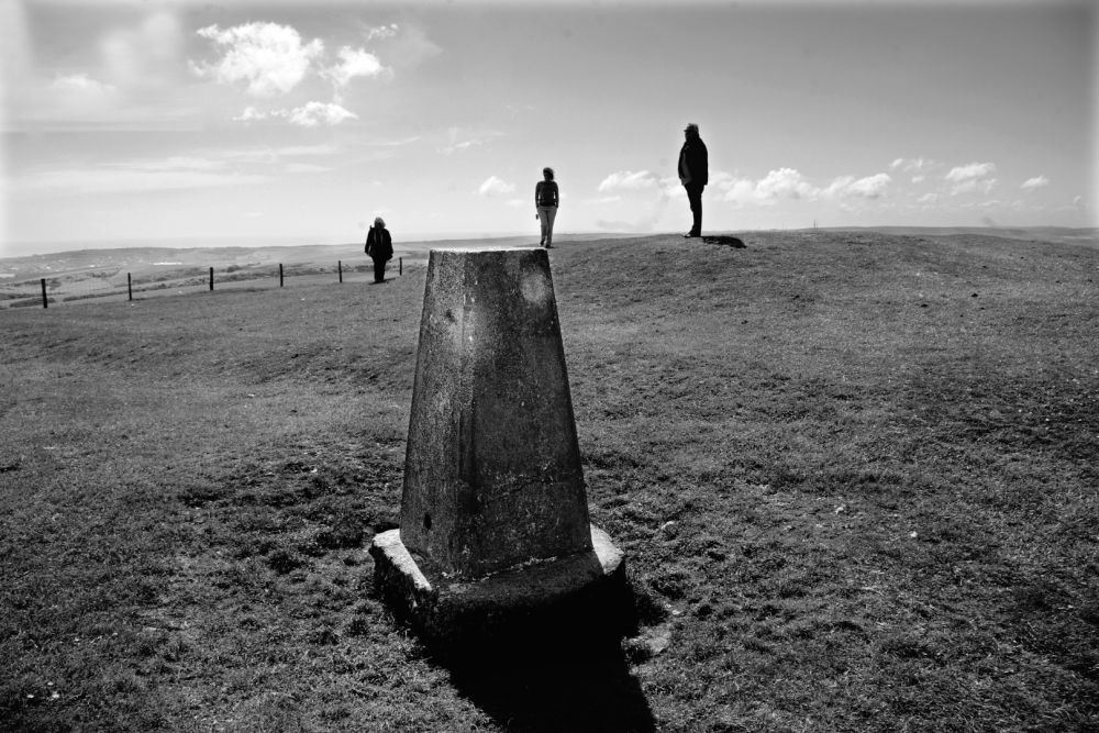 Three People and a Trig Point